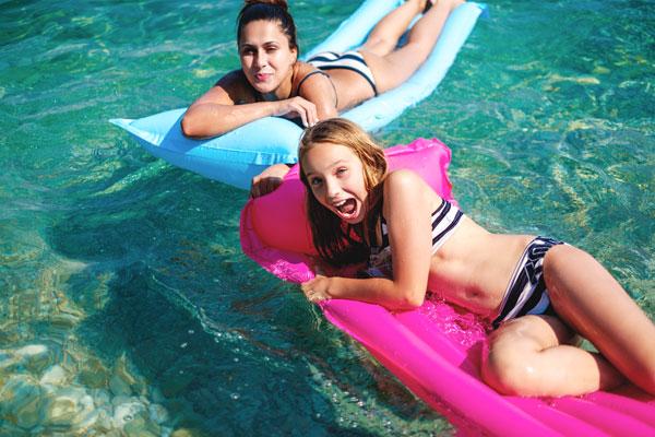 Mutter und Tochter auf Luftmatratzen im Badesee