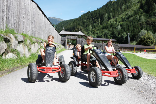 Kinder auf Go-Karts auf dem Campingplatz