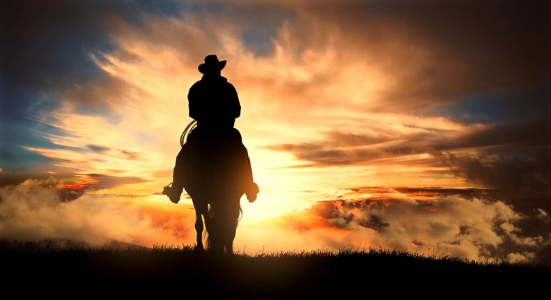 Cowboy in der Prärie reitet dem Sonnenaufgang entgegen