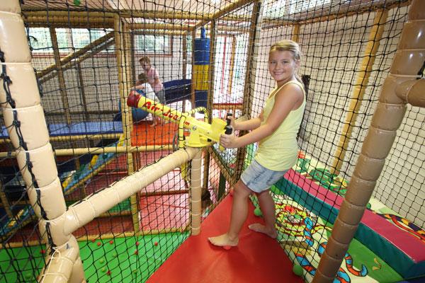 Mädchen an der Ballkanone im Kinderspielhaus
