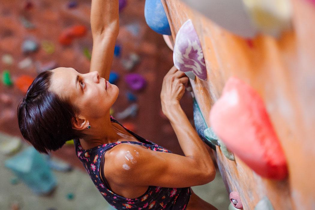 Frau an der Kletterwand in der Kletterhalle in Camping Aufenfeld