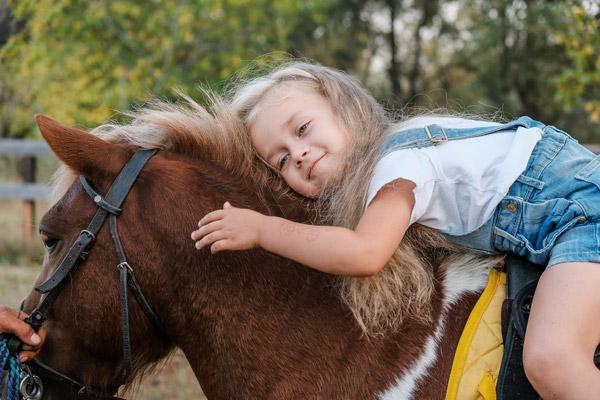 Mädchen sitzt auf einem Pferd auf dem Reitgelände des Freizeitpark Aufenfeld