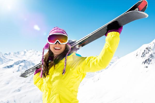glückliche Frau mit Ausrüstung vom Skiverleih Camping Aufenfeld