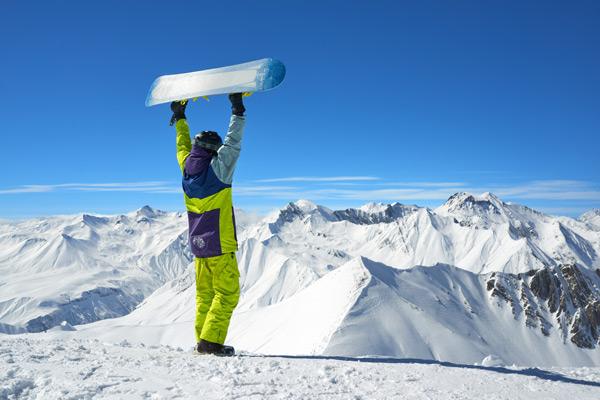 Mann mit Snowboard aus dem Skiverleih Camping Aufenfeld auf dem Berg