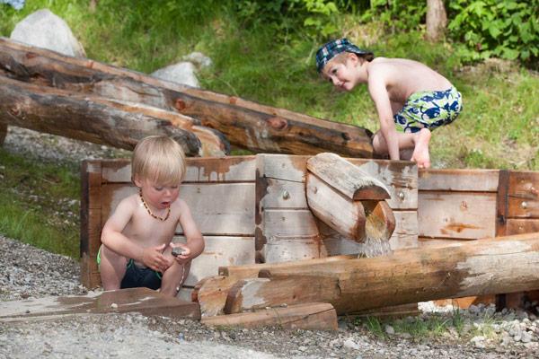 Kinder spielen Wasserspiele nahe der Hütte Zillertal